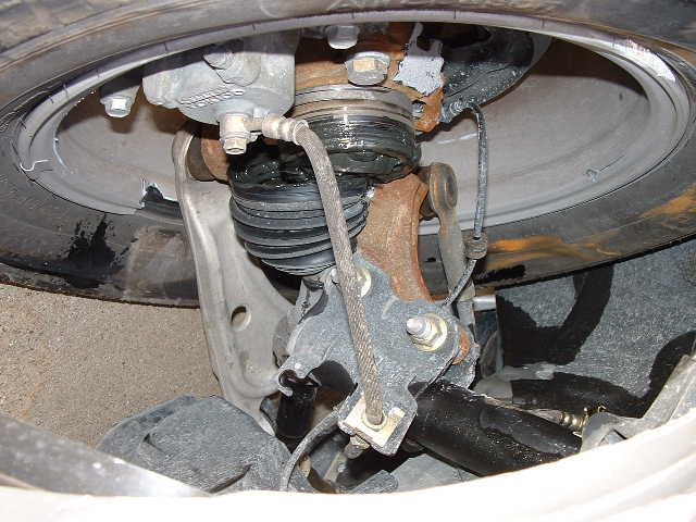 Major mechanical damage here. Note the broken steering knuckle, wheel, and the damaged brake system.